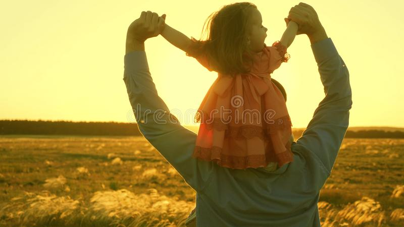 Dad dancing on his shoulders with his daughter in sun. Father travels with baby on his shoulders in rays of sunset. A. Dad dancing on his shoulders with his royalty free stock images