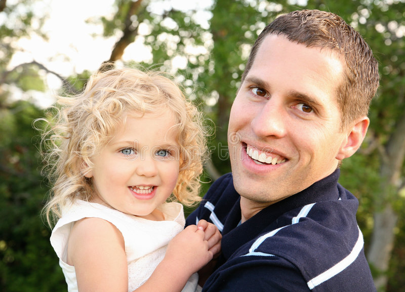 Dad and Daughter. Young Caucasian father holding his two year old daughter outdoors in Spring and smiling