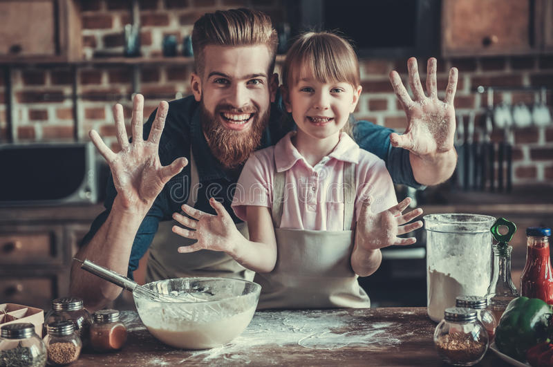 Dad and daughter cooking. Cute little girl and her handsome bearded dad in aprons are having fun with flour, looking at camera and smiling while cooking in stock images