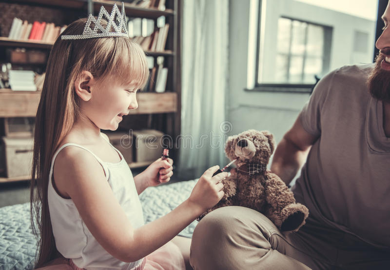 Dad and daughter. Cute little girl and her handsome bearded dad are playing in her room. Girl is doing teddy bear makeup