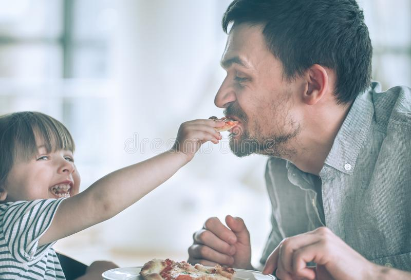 Dad and daughter eat pizza. At a table in a cafe, celebrate his father`s day, family values royalty free stock photos