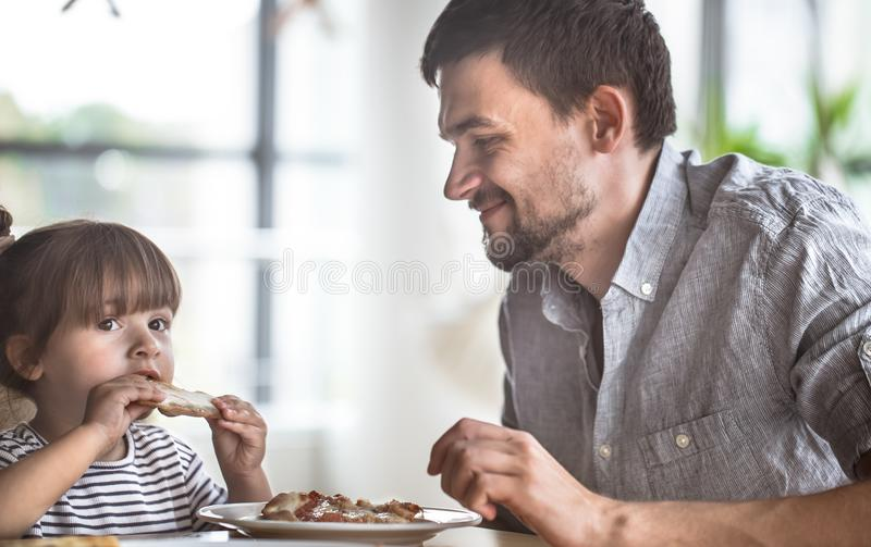 Dad and daughter eat pizza. At a table in a cafe, celebrate his father`s day, family values royalty free stock images