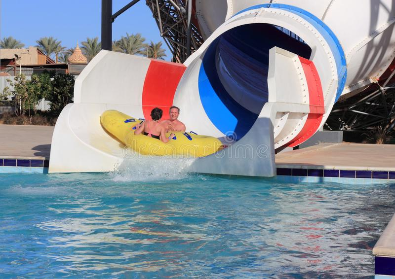Dad and daughter fun, actively and emotionally ride on a roller coaster in the water park royalty free stock images