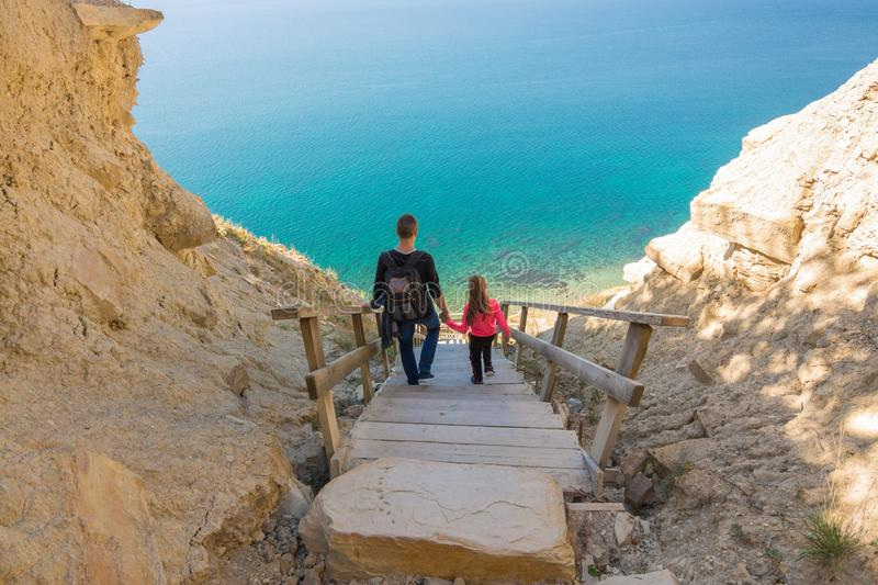 Dad and daughter go down the steep mountain stairs to the sea stock image