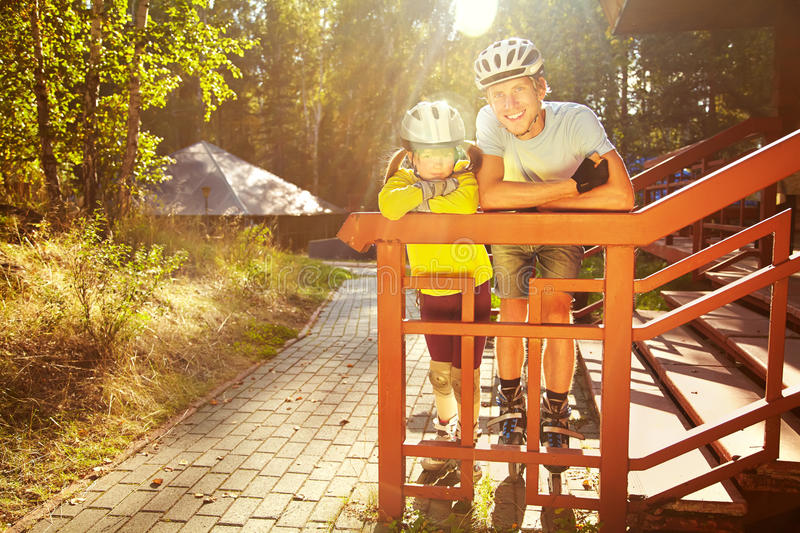 Dad and daughter in a helmet. Portrait of a sports dad and daughter in a helmet. Dad with his little daughter on the skates. two people rollerblade stock photography