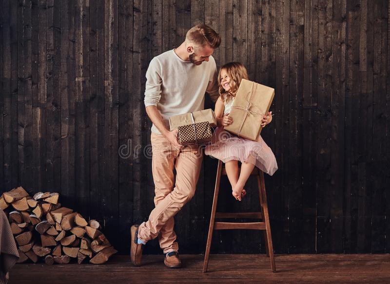 Dad and daughter holds gifts in empty room against a wooden wall. royalty free stock photo