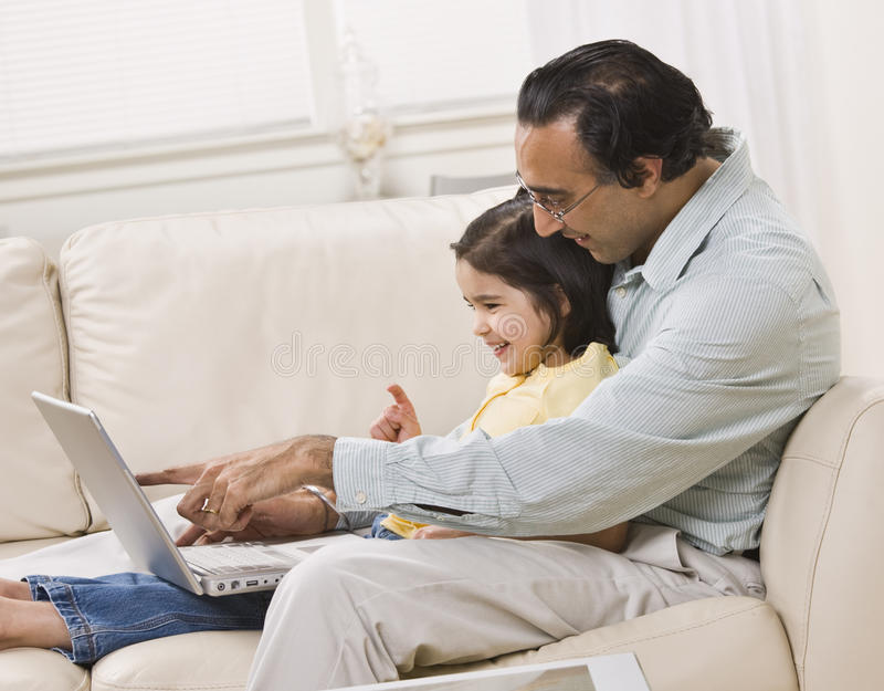 Dad and Daughter Look at Laptop stock photography