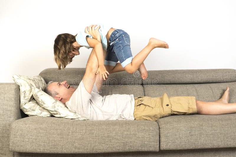 Dad and daughter playing at home. Dad lying on sofa and lifting up his daughter stock image