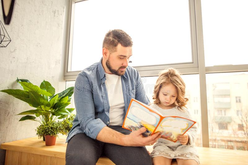 Dad and daughter reading a book at home stock photo