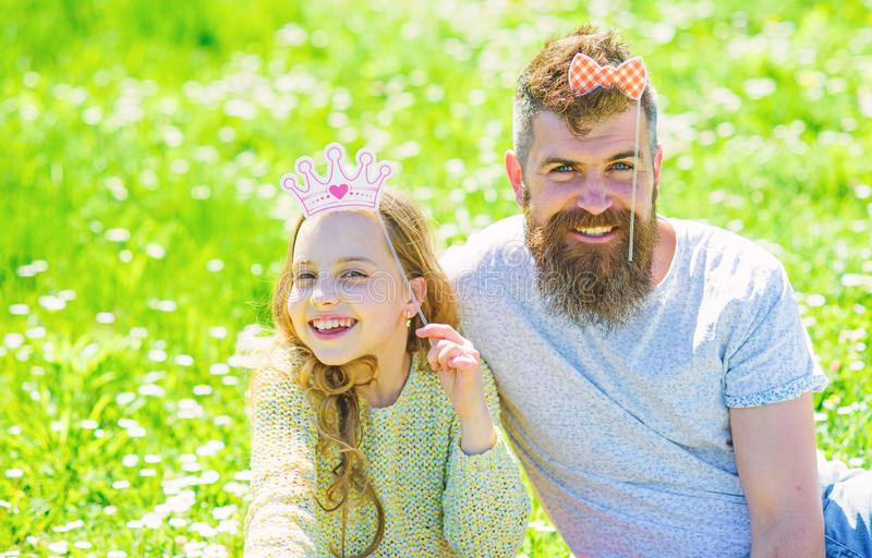 Dad and daughter sits on grass at grassplot, green background. Child and father posing with crown and bow photo booth. Attributes. Fatherhood concept. Family royalty free stock images