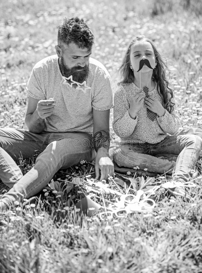 Dad and daughter sits on grass at grassplot, green background. Child and father posing with eyeglases and muastache. Photo booth attributes. Family time concept stock photo