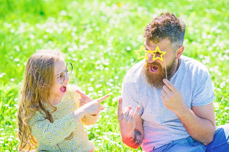 Dad and daughter sits on grass at grassplot, green background. Child and father posing with eyeglases photo booth. Attribute while speaking. Negotiation concept stock images