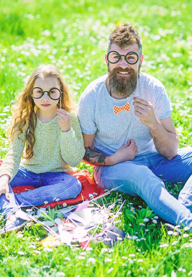 Dad and daughter sits on grass at grassplot, green background. Child and father posing with eyeglases photo booth. Attributes at meadow. Family spend leisure stock photo