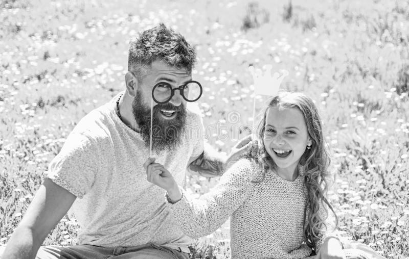 Dad and daughter sits on grass at grassplot, green background. Daddys princess concept. Child and father posing with. Crown and eyeglasses photo booth stock photography