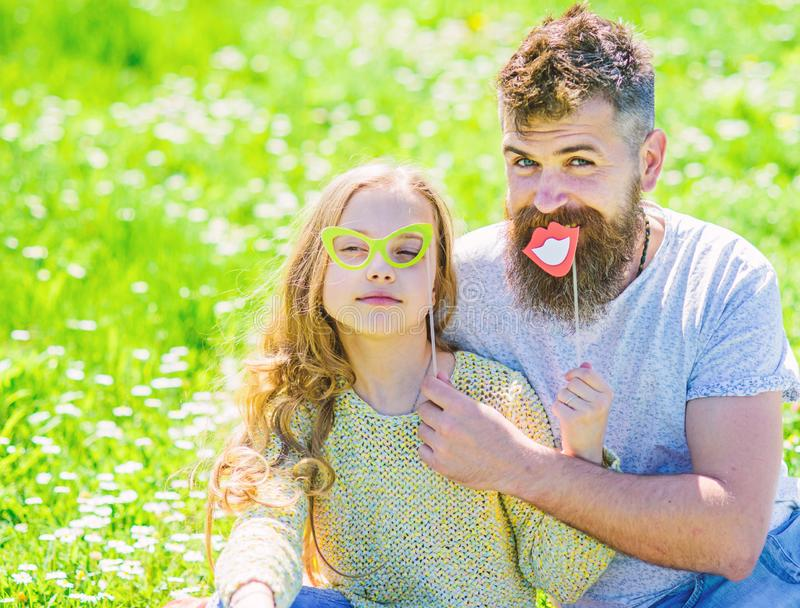 Dad and daughter sits on grass at grassplot, green background. Family spend leisure outdoors. Child and father posing. With eyeglases and lips photo booth stock images
