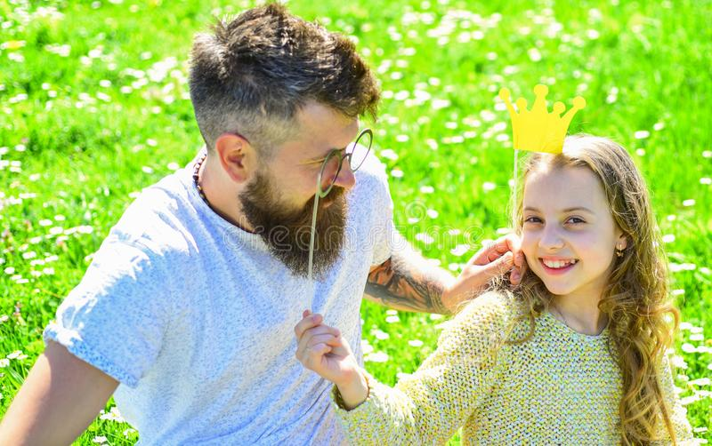 Dad and daughter sits on grass at grassplot, green background. Family spend leisure outdoors. Daddys princess concept. Child and father posing with crown and royalty free stock photography