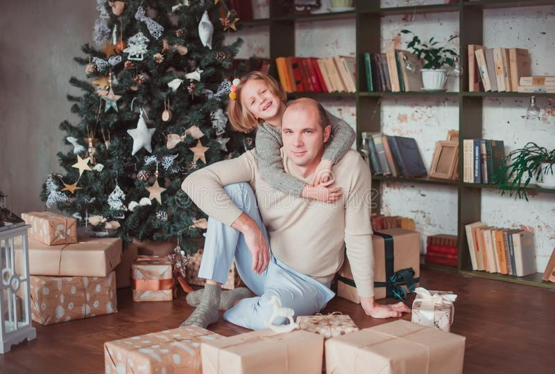 Dad and daughter sitting at the Christmas tree. Daughter hugging dad`s neck. Lie near the boxes with gifts. Warm colour stock photo