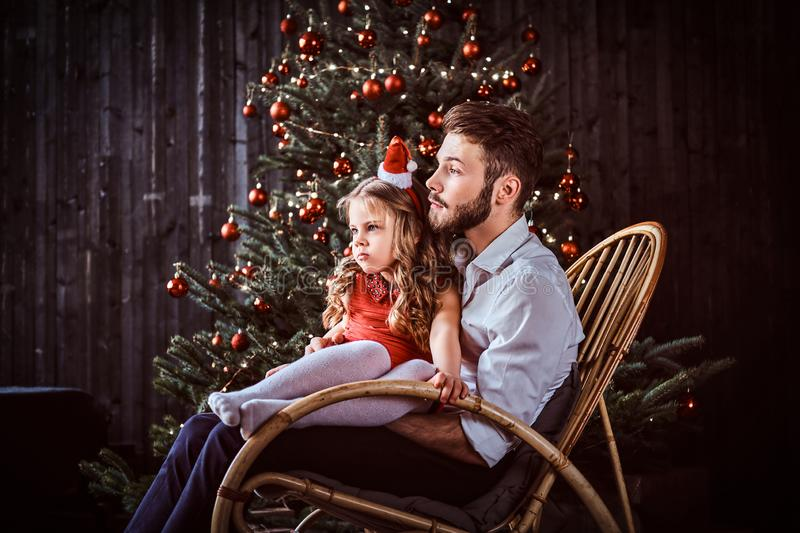 Dad and daughter sitting together on a rocking chair near a Christmas tree at home. stock image