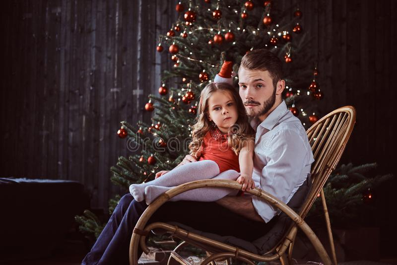 Dad and daughter sitting together on a rocking chair near a Christmas tree at home. royalty free stock photos
