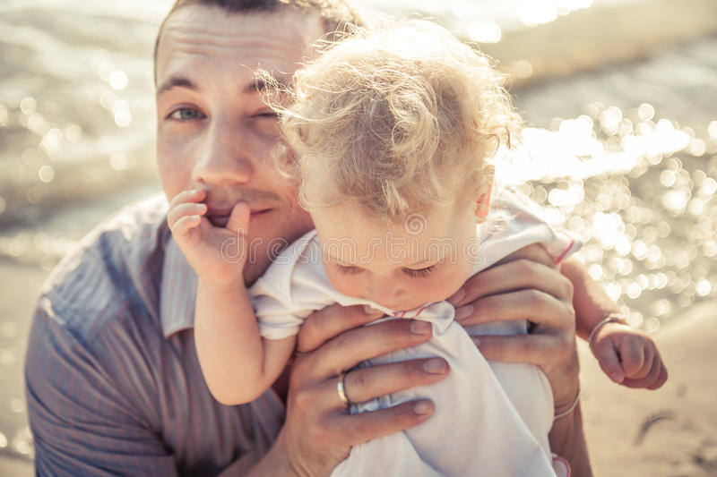 Dad and daughter together on the beach coast during holidays with shining sea on background. Father embrace child. Soft focus on father face stock images