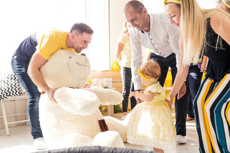 Dad gives the girl a big toy bear. Photo of Dad gives the girl a big toy bear stock photos