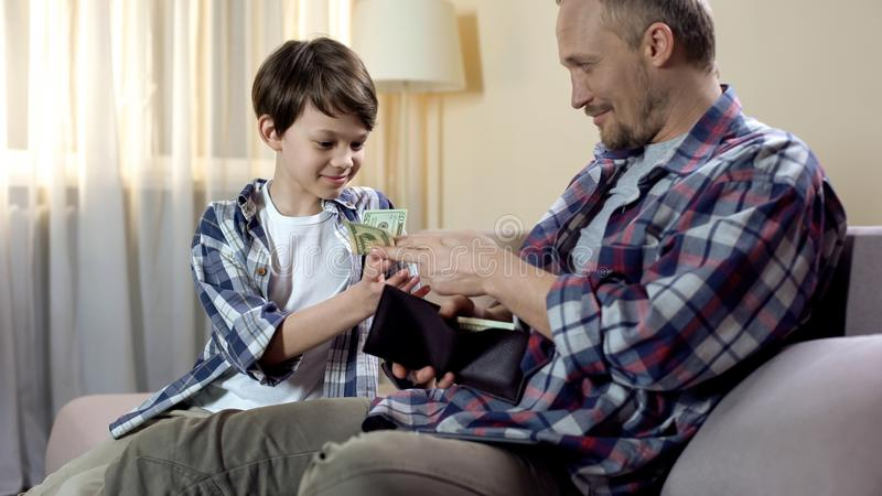 Dad giving cash from wallet to son for new toys, child pocket money, finances royalty free stock photo