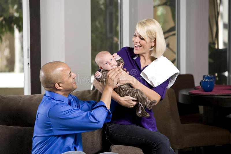 Dad handing baby to mom with burp cloth. Dad handing 3 month old baby to mom for feeding royalty free stock photos