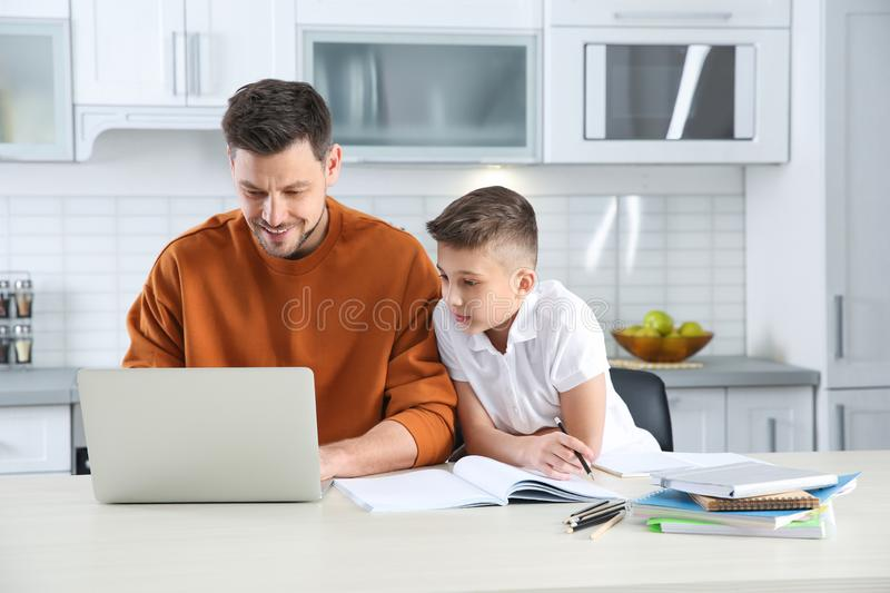 Dad helping his son with homework. In kitchen stock image