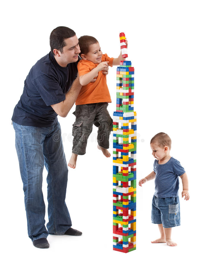 Dad helping his sons. To finish the plastic building tower royalty free stock photo