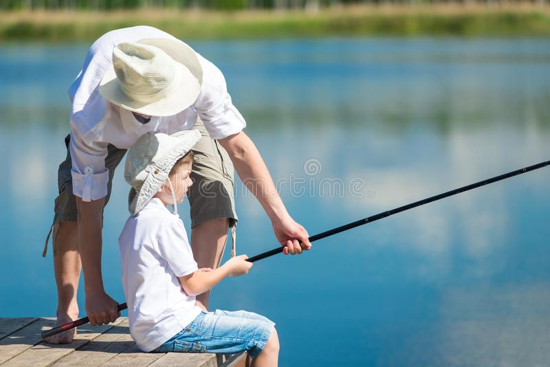 Dad helps his son catch fish with a fishing rod on the river stock photography