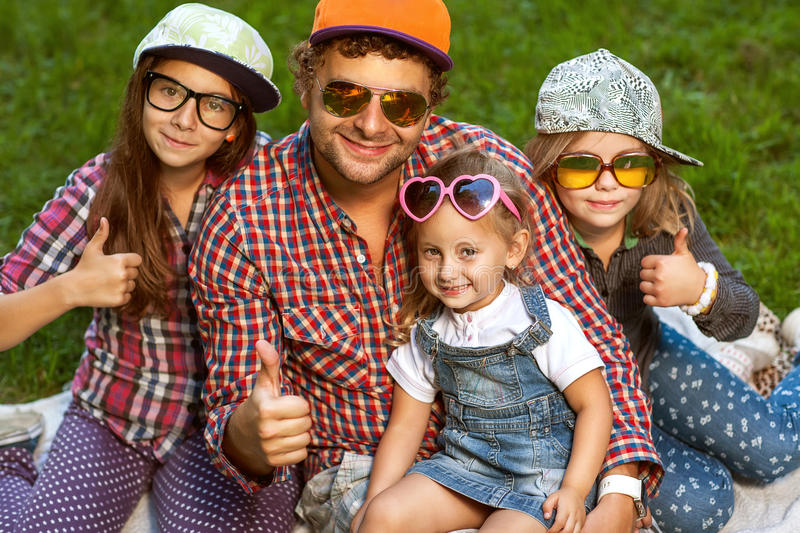 Dad and his 3 daughters. Lie on the grass in sunglasses happy. hipster Style stock photos