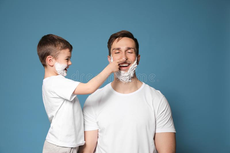 Dad and his little son having fun with shaving foam on faces. Against color background royalty free stock images