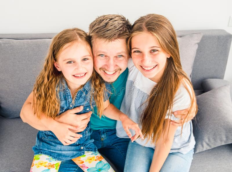 Dad and his two smiling daughters stock photo