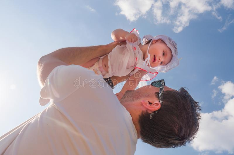 Dad holds a child over his head. Half a year old baby. Walk down the street. Summer day royalty free stock photo