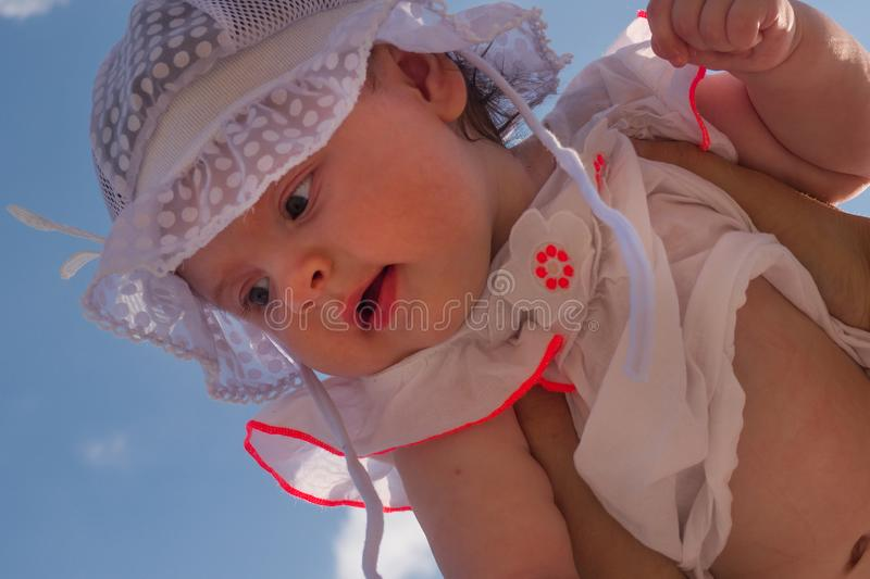 Dad holds a child over his head. Half a year old baby. Walk down the street. Summer day royalty free stock photos