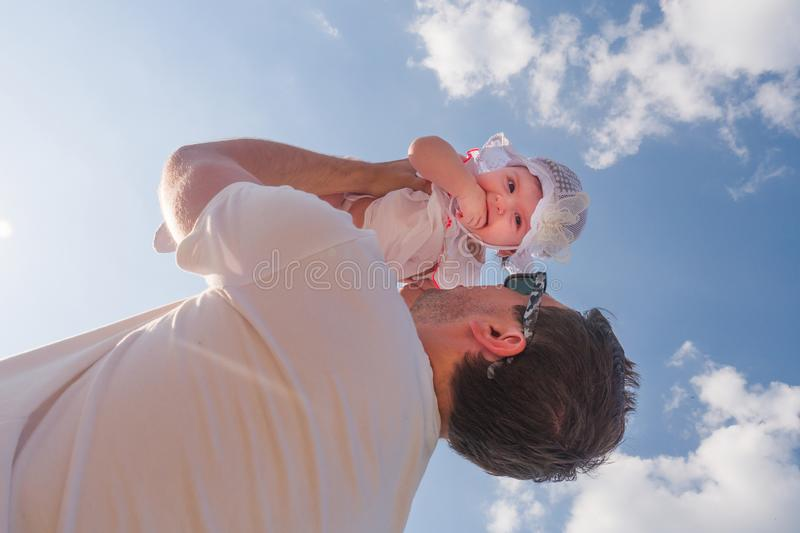 Dad holds a child over his head. Half a year old baby. Walk down the street. Summer day royalty free stock photography