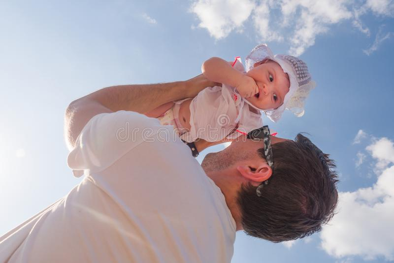 Dad holds a child over his head. Half a year old baby. Walk down the street. Summer day stock images