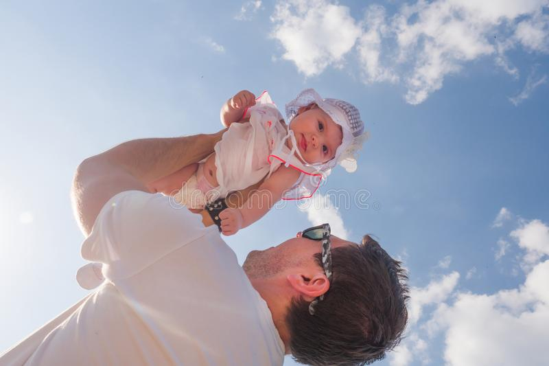 Dad holds a child over his head. Half a year old baby. Walk down the street. Summer day stock photos