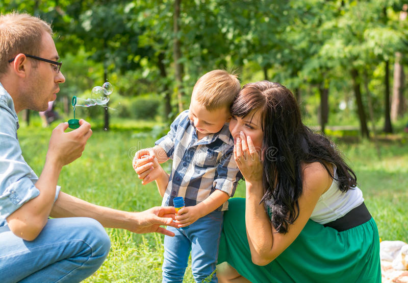 Dad holds his son`s hand and teaches him to blow soap bubbles. M. Om sits by and looks. Family resting in the park royalty free stock image