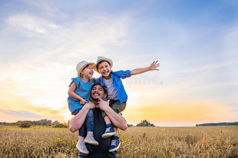 Dad holds two children in his arms. happy family playing in the field in the evening sunset. Children laugh with happiness father frolics with his daughter and royalty free stock photos