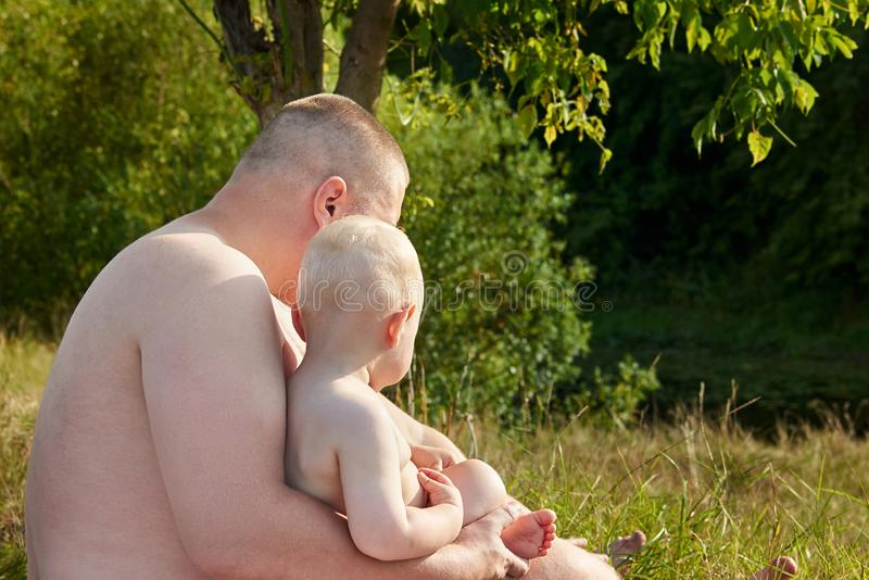 Dad hugs his little son on the banks of the river on a hot summer day. Side view. Dad hugs his little cute son on the banks of the river on a hot summer day stock photography