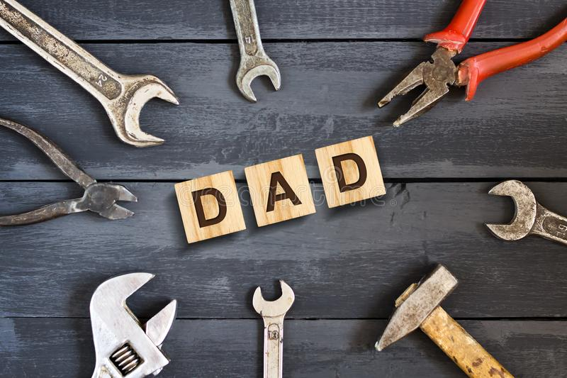Dad inscription on wooden cubes with working tools on a wooden background.Happy fathers day concept. Greetings and gifts stock photo
