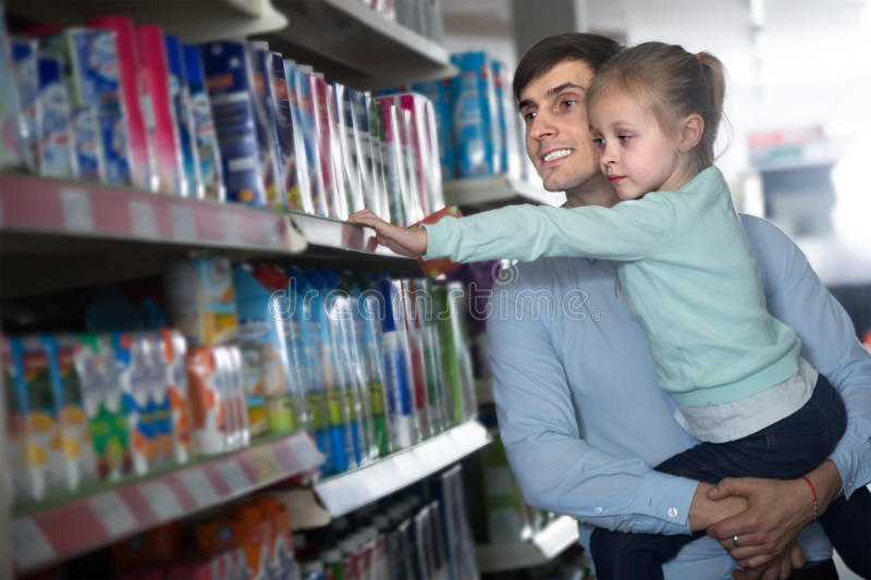 Dad keeps daughter in her arms in a supermarket. Dad keeps daughter in her arms near the shelves with products in a supermarket stock image