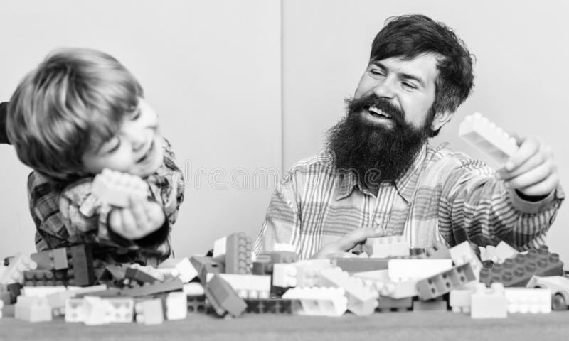 Dad and kid build plastic blocks. Child care development. Family leisure. Father son game. Father and son create royalty free stock photo