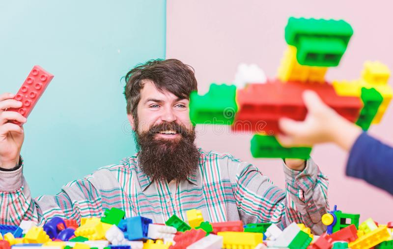 Dad and kid build plastic blocks. Child care and upbringing. Father son game. Father son create constructions. Father stock photos