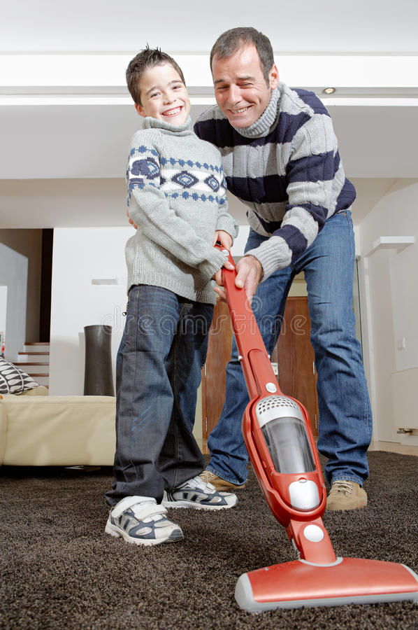 Dad and kid cleaning. Dad and son vacuum cleaning their living room, smiling and bonding stock photography