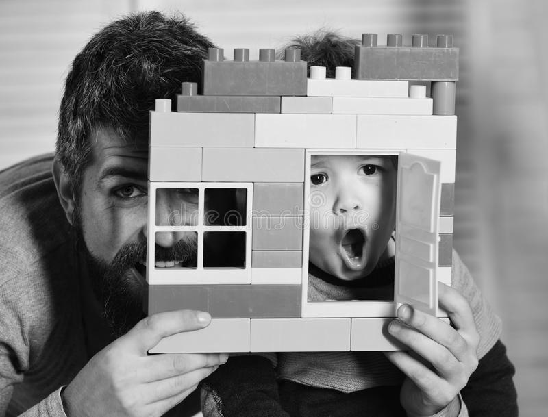 Dad and kid with hide behind building wall made of plastic blocks. Boy and man play together. Father and son with royalty free stock photo