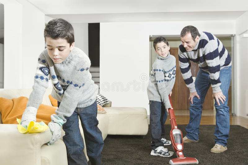 Dad and Kids cleaning. Dad and twin sons cleaning their home's living room royalty free stock images