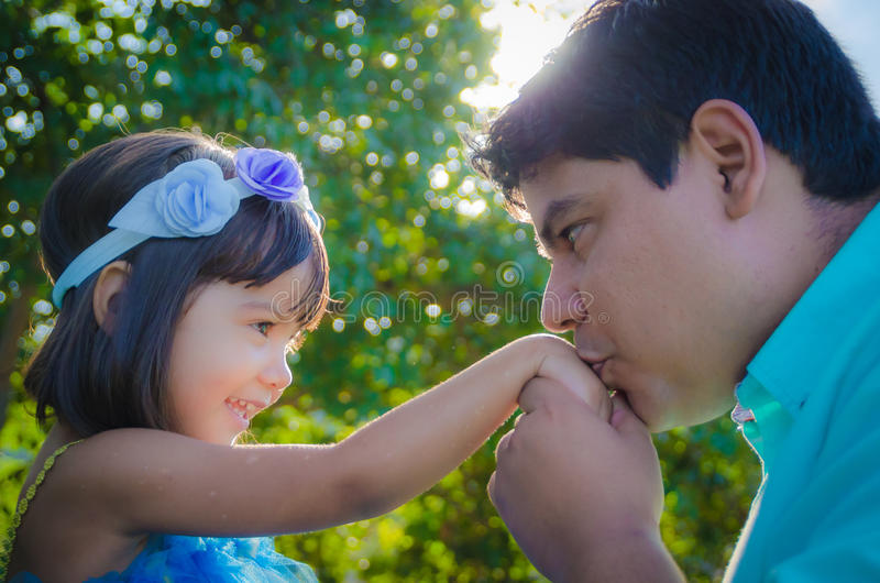Dad kissing dauther hand. In the park, sun in the back