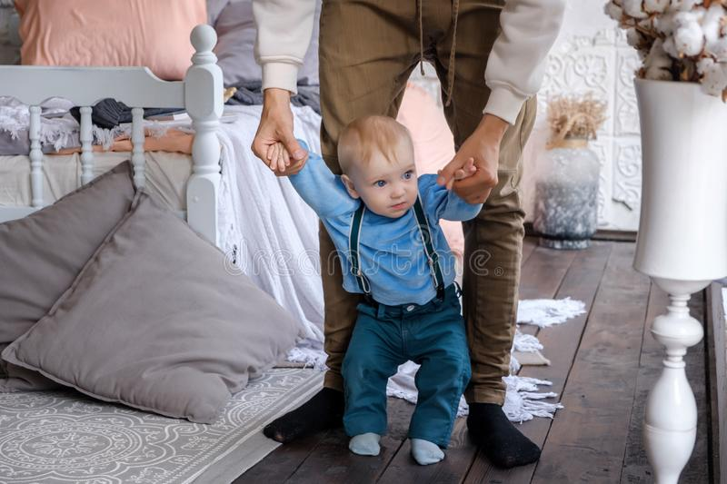 Dad leads his little son by the arms so he doesn `t fall.  royalty free stock photo